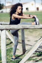 Sporty young woman stretching outdoors - JSMF00834