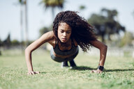 Sporty young woman doing push-ups on lawn - JSMF00846