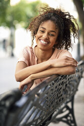 Portrait of happy young woman sitting on a bench - JSMF00858