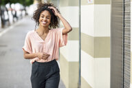 Portrait of smiling young woman in the city - JSMF00867