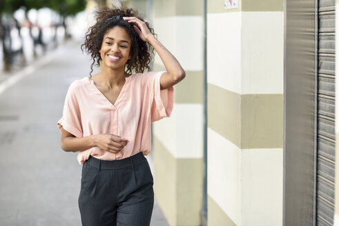 Spain, Andalusia, Jerez de la Frontera, Happy young black woman with curly hair smiling in urban street. Lifestyle concept. - JSMF00867