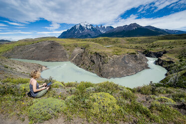 Chile, Patagonia, woman using tablet at a river bend in Torres del Paine National Park - RUNF01478