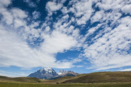 Chile, Patagonia, Torres del Paine National Park, meadow and mountains under cloudy sky - RUNF01481