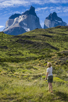 Chile, Patagonia, woman standing on medow in Torres del Paine National Park - RUNF01484