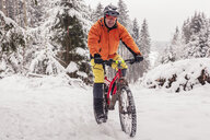 Portrait of happy man riding mountainbike on path in winter forest - SEBF00042