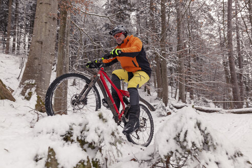 Man riding mountainbike on path in winter forest - SEBF00048