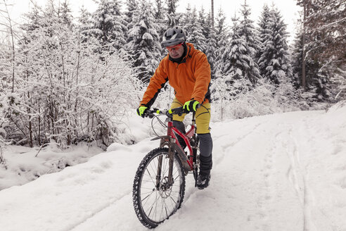 Man riding mountainbike on path in winter forest - SEBF00051