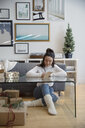 Young woman wrapping Christmas gifts and writing in card in living room - HEROF28496