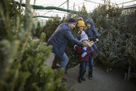 Family taking selfie, shopping for Christmas tree at Christmas market - HEROF28544