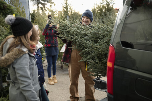 Worker helping family load Christmas tree into SUV at Christmas market - HEROF28595