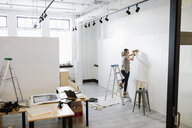 Female gallery owner drilling hole in wall, preparing for exhibition - HEROF28667