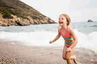 Cute girl running on beach, Portoferraio, Tuscany, Italy - CUF49770