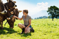 Woman bonding with herd of cows on field, Sonthofen, Bayern, Germany - CUF49863