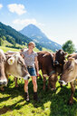 Woman bonding with herd of cows on field, Sonthofen, Bayern, Germany - CUF49866