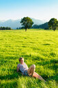 Woman lying down on grass in countryside, Sonthofen, Bayern, Germany - CUF49902