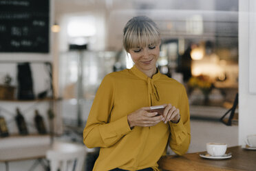 Blond businesswoman using smartphone in a coffee shop, reading text messages - JOSF03158