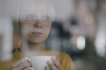 Portrait of a beautiful blond woman standing at window, drinking coffee - JOSF03167
