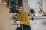 Blond businesswoman using smartphone in a coffee shop, reading text messages - JOSF03170