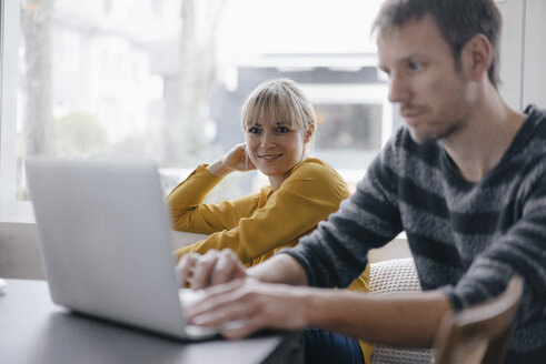Man and woman sitting at table, using laptop - JOSF03179