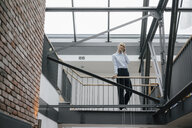 Businesswoman leaning on railing, talking on the phone - JOSF03185