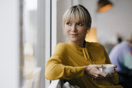Portrait of a beautiful blond woman,sitting at window, drinking coffee - JOSF03188