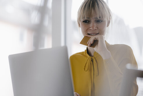 Blond woman doing online payment with her credit card - JOSF03212