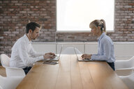 Businessman and woman sitting at desk, working on laptop - JOSF03236