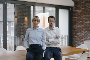 Successful businessman and woman standing in office, with arms crossed - JOSF03242
