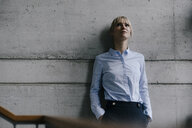 Businesswoman leaning on concrete wall, looking up - JOSF03251