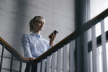 Businesswoman leaning on railing, using smartphone - JOSF03254