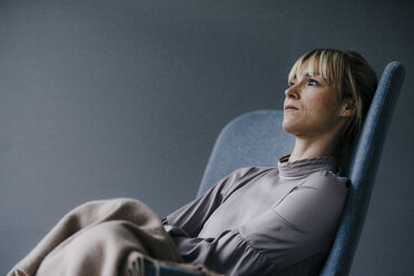 Blond woman sitting in armschair, looking sad - JOSF03263