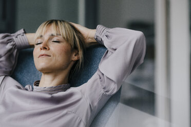 Blond woman relaxing in armchair, with hands behind head - JOSF03266