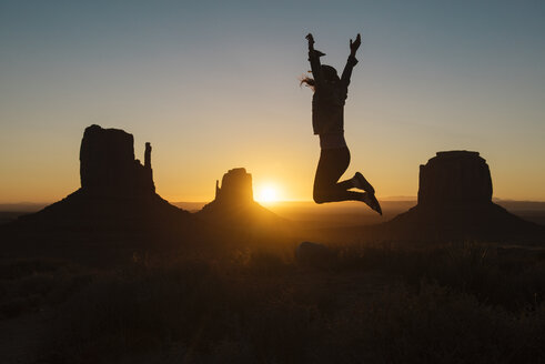 USA, Utah, Monument Valley, silhouette of happy woman jumping in the air at sunrise - GEMF02887