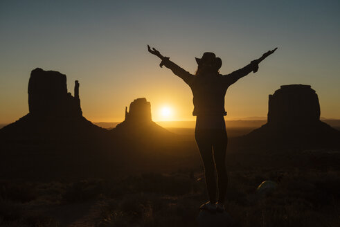 USA, Utah, Monument Valley, silhouette of happy woman with cowboy hat enjoying sunrise - GEMF02890
