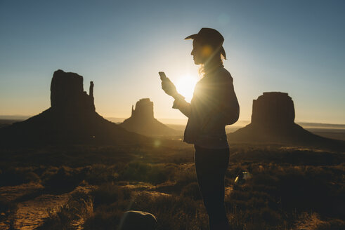 USA, Utah, Monument Valley, silhouette of woman with cowboy hat looking at mobile phone at sunrise - GEMF02899