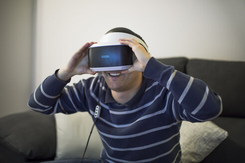 Laughing young man on couch at home using VR glasses - ACPF00487