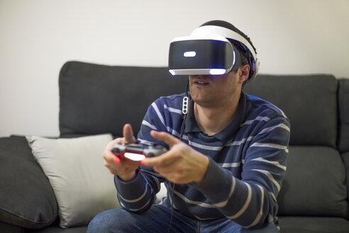Young man wearing VR glasses sitting on couch at home playing video game - ACPF00490