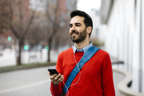 Casual businessman commuiting in the city, using earphones and smartphone - JRFF02838
