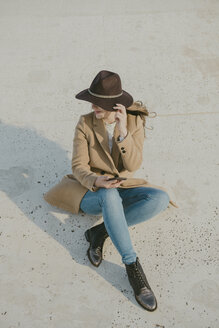 Young hipster woman sitting on the ground holding a phone - AHSF00046