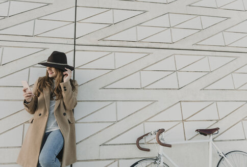 Young hipster woman near to a bicycle holding a phone - AHSF00058
