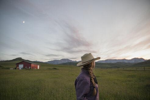 Pensive female rancher watching dramatic sunset sky field - HEROF28720
