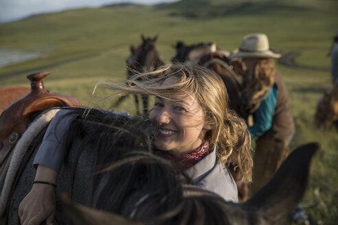 Portrait smiling female rancher hugging horse in field - HEROF28723