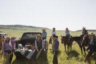Portrait female ranchers with horses enjoying truck bed picnic - HEROF28726