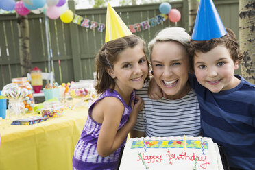 Portrait mother and kids with birthday cake backyard - HEROF28735