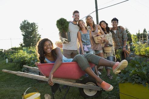 Portrait smiling friends harvesting vegetables in community garden - HEROF28750