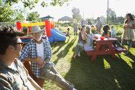 Men talking at neighborhood park party - HEROF28765
