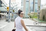 Portrait confident businesswoman turning crossing urban crosswalk - HEROF28780