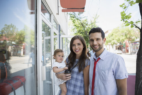 Portrait smiling family window shopping at storefront - HEROF28786