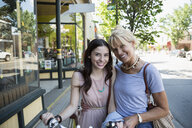 Portrait smiling mother and daughter outside storefront - HEROF28789