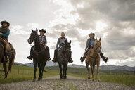 Female ranchers horseback riding on remote road - HEROF28825